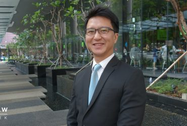 an image of Singapore lawyer Lau Kah Hee with a picturesque hotel in the background