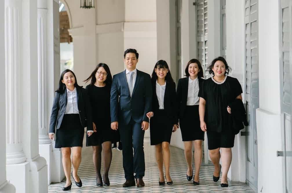 Photograph of the lawyers of DCMO (Dorothy Chai & Mary Ong) Law Practice in Singapore walking down a corridor